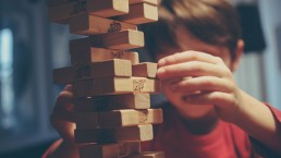 boy-removing-jenga-block-from-jenga-tower