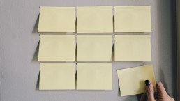 hand-removing-yellow-sticky-note-from-tiled-notes
