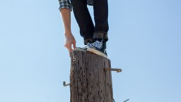 man-standing-precariously-on-top-of-pole