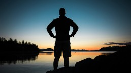 sillhoueted-custom-app-developer-standing-arms-akimbo-looking-heroically-at-lake